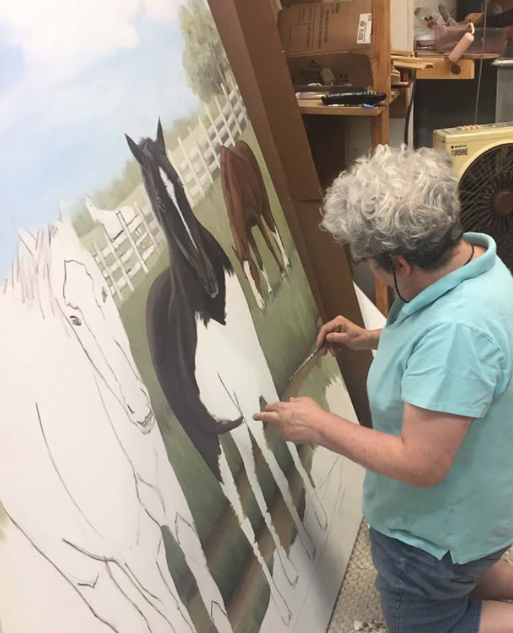 Sharon painting mural with horses