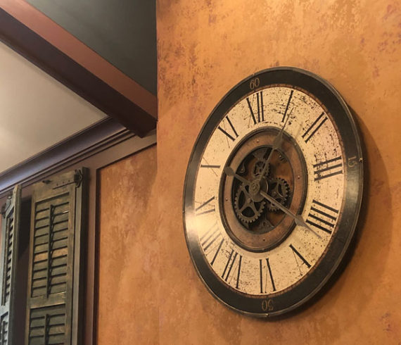 Clock on wall and green cast ceiling